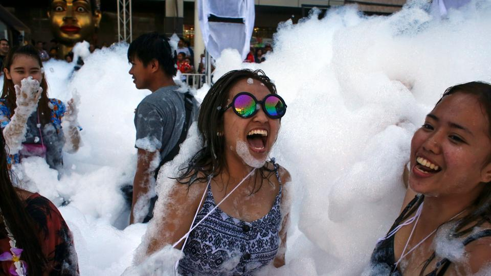 Revellers react at a foam party during Songkran Festival celebrations in Bangkok. Major streets are closed to traffic as they become the center for such foam and water fight parties. (REUTERS)