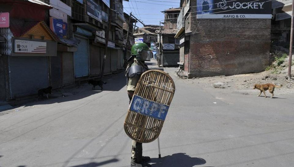 An paramilitary soldier stands guard during curfew in Srinagar.