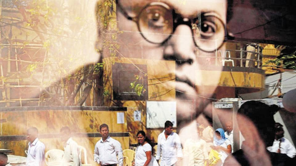 People are reflected on the glass of a framed photograph of BR Ambedkar, as they visit a memorial dedicated to him, on his birth anniversary in Mumbai on April 14, 2016.