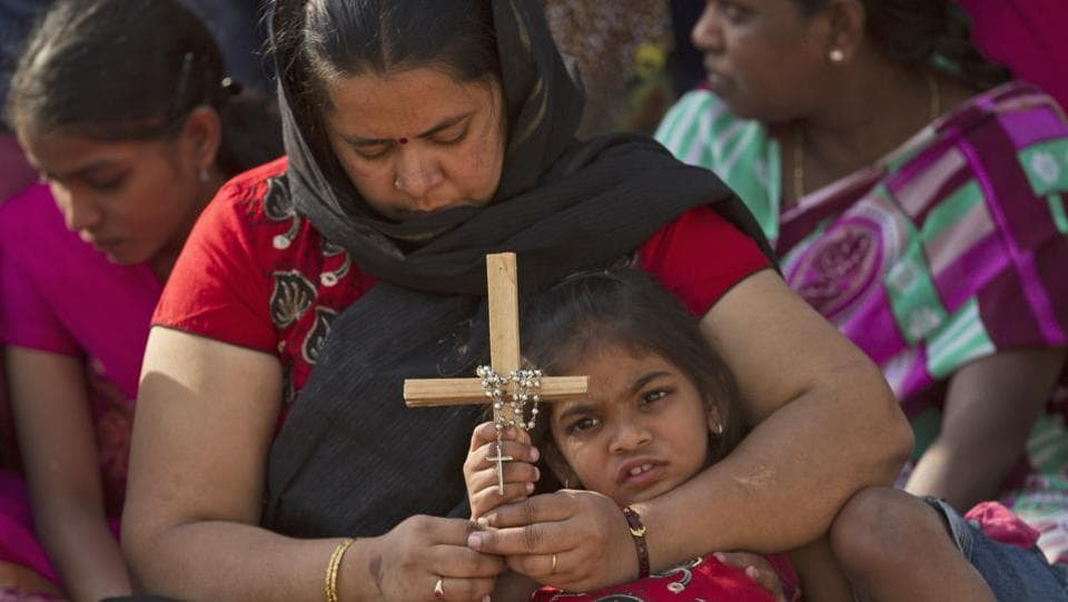 An Indian mother and daughter pray as they watch the re-enacting of the crucifixion of Jesus Christ during Good Friday in Hyderabad, India. (Mahesh Kumar / AP)