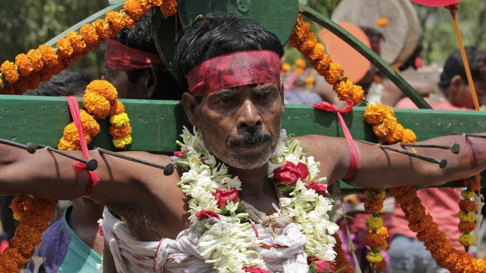 A Hindu devotee stands with nails pierced through his skin during Charak festival procession in Hooghly village, on the outskirts of Kolkata. (Bikas Das / AP)