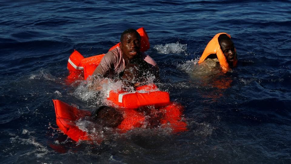 Migrants try to stay afloat after falling off their rubber dinghy. (Darrin Zammit Lupi / Reuters)