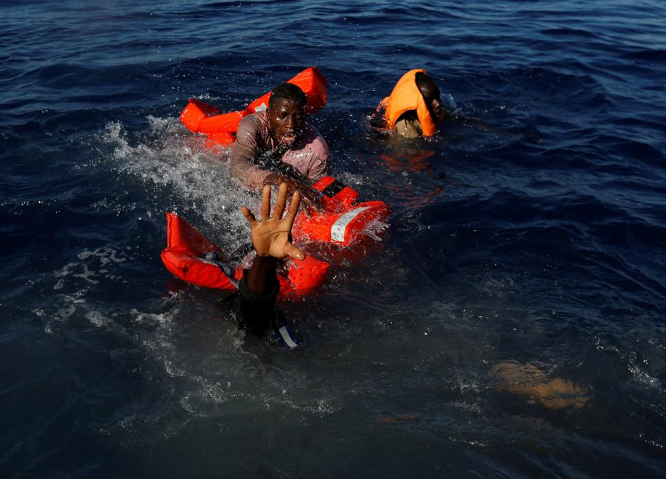Migrants try to stay afloat after falling off their rubber dinghy during a rescue operation by the Malta-based NGO Migrant Offshore Aid Station (MOAS) ship in the central Mediterranean in international waters some 15 nautical miles off the coast of Zawiya in Libya. (Darrin Zammit Lupi / Reuters)