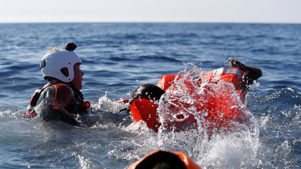 A rescue swimmer holds onto migrants frantically trying to stay afloat after falling off their rubber dinghy. (Darrin Zammit Lupi / Reuters)