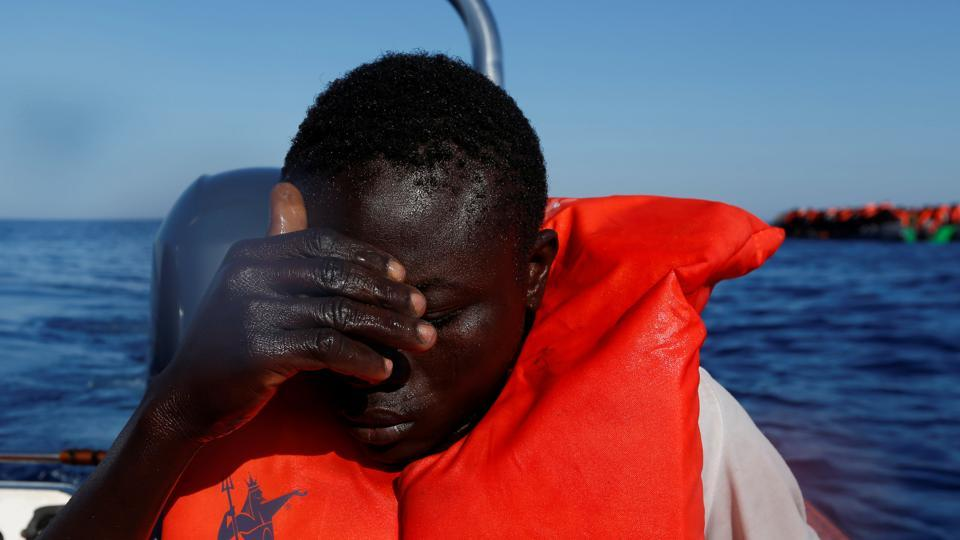 A migrant reacts after being pulled out of the sea after falling off a rubber dinghy. (Darrin Zammit Lupi / Reuters)