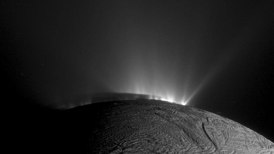 Rows of plumes rise from ice fractures on the surface of Enceladus, a moon orbiting Saturn.