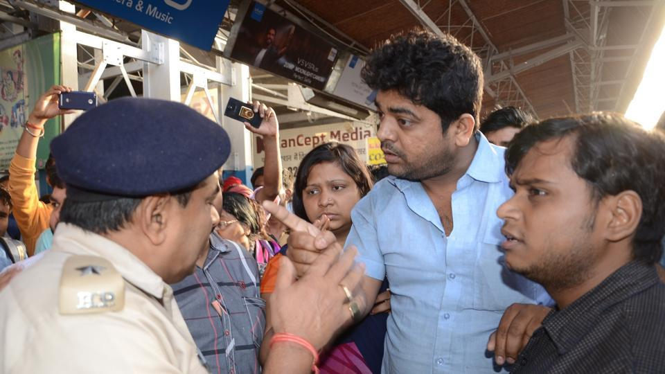 Passengers argue with a railway cop at Patna junction after their belongings were stolen on the Rajdhani Express .