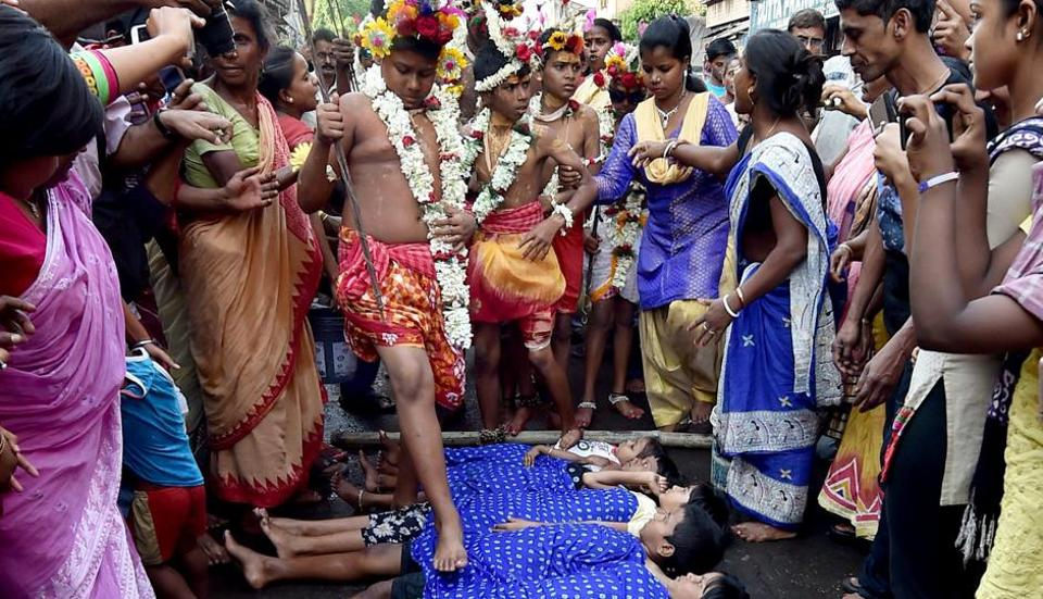 Children lie on the Road as Hindu devotees bless them by touching with feet during Charak or Shiva Gajan festival in Kolkata. (PTI)