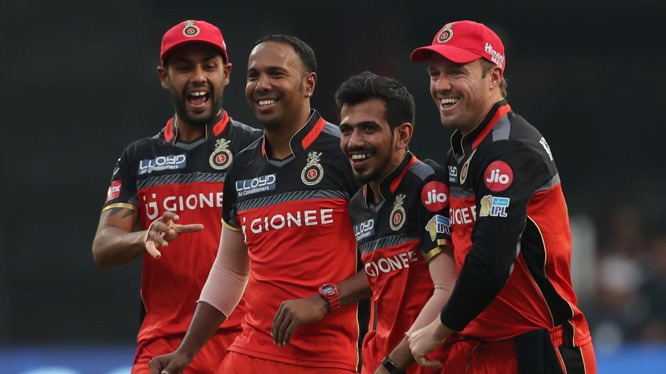 Royal Challengers Bangalore captain Virat Kohli celebrates the dismissal of Mitchell McClenaghan with Samuel Badree.  (BCCI)