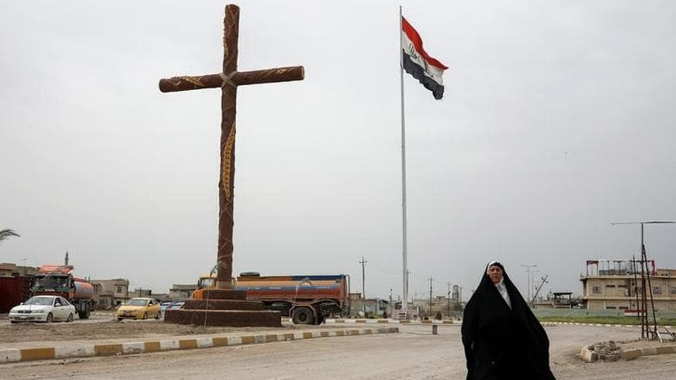 A woman walks past a big cross at the entrance of the town of Qaraqosh. Shi'ites in the Iraqi government forces and paramilitary groups, mostly from further south in the country, has scribbled such slogans on buildings all over Mosul too. Soldiers have also hoisted the flag of Ali in the city and on their on military vehicles.  (Marko Djurica/Reuters)