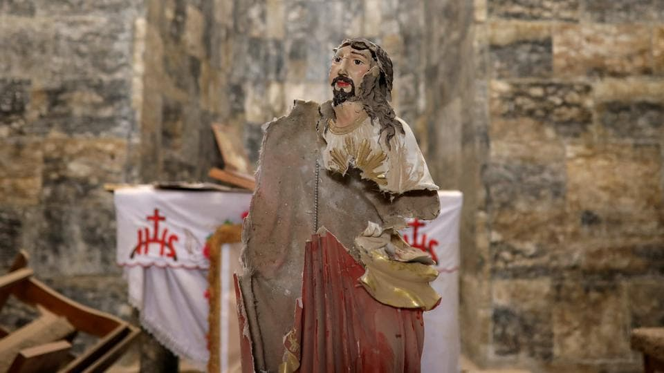 A damaged statue of Jesus Christ is seen inside a church. Germany alone took in 130,000 Iraqis, among them many Christians, in 2015 and 2016. But, most ended up in Erbil with relatives or in homes paid for by aid agencies. (Marko Djurica/Reuters)