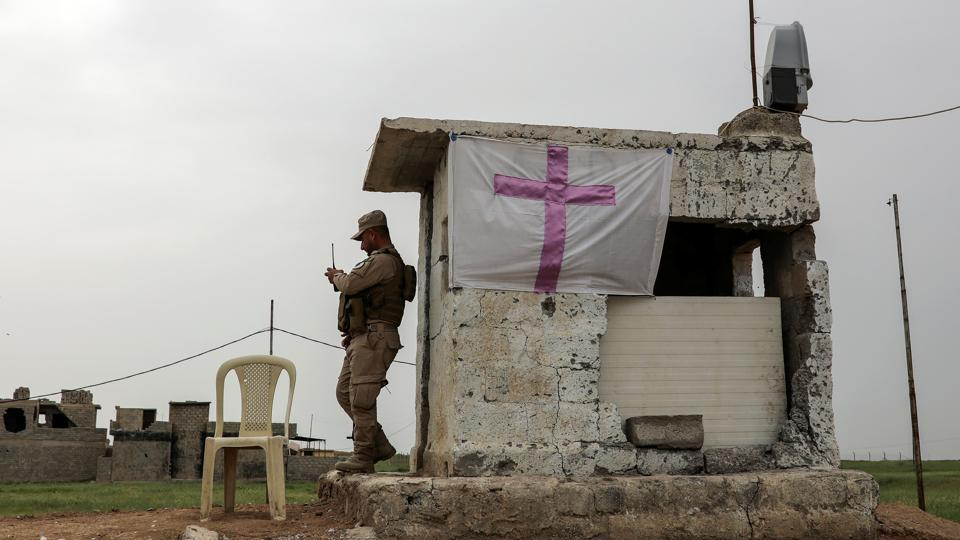 A Iraqi solider stands by a flag with a cross at a check point. Whether more Christians can live permanently in Qaraqosh depends on whether the security forces win their trust. Army and police have tried to ease fears by stationing soldiers in front of churches, and even helping Christian volunteers to set up a massive cross at the town's entrance. (Marko Djurica/Reuters)
