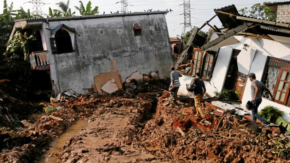People walk past damaged houses during a rescue mission after a garbage dump collapsed and buried dozens of houses in Colombo.