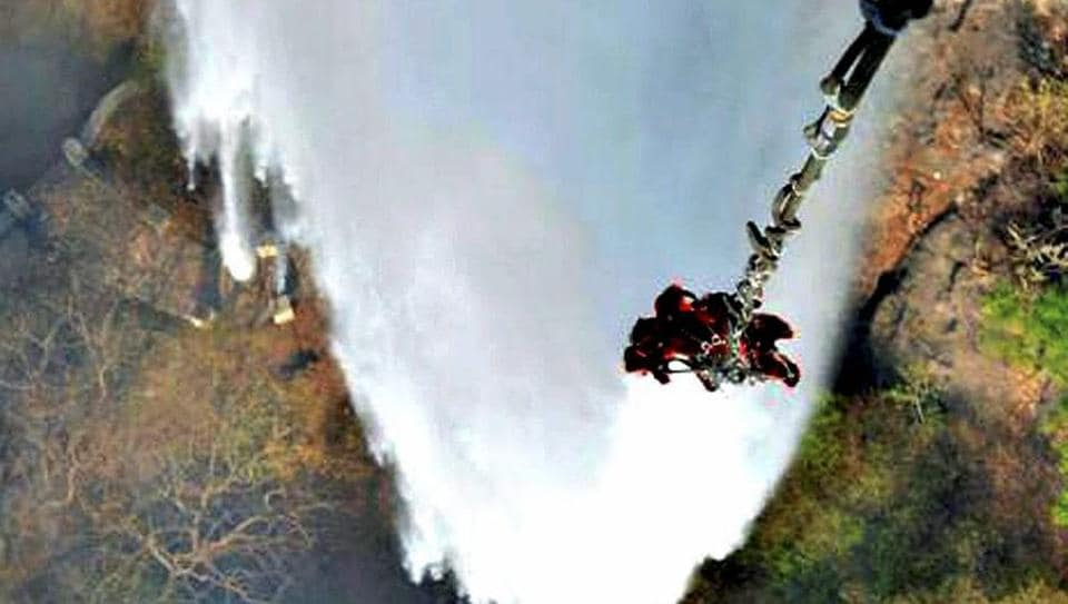 Helicopters of Indian Air Force pour water with the help of their bambi buckets in a bid to douse the raging forest fires in Mount Abu, Rajasthan on Saturday.