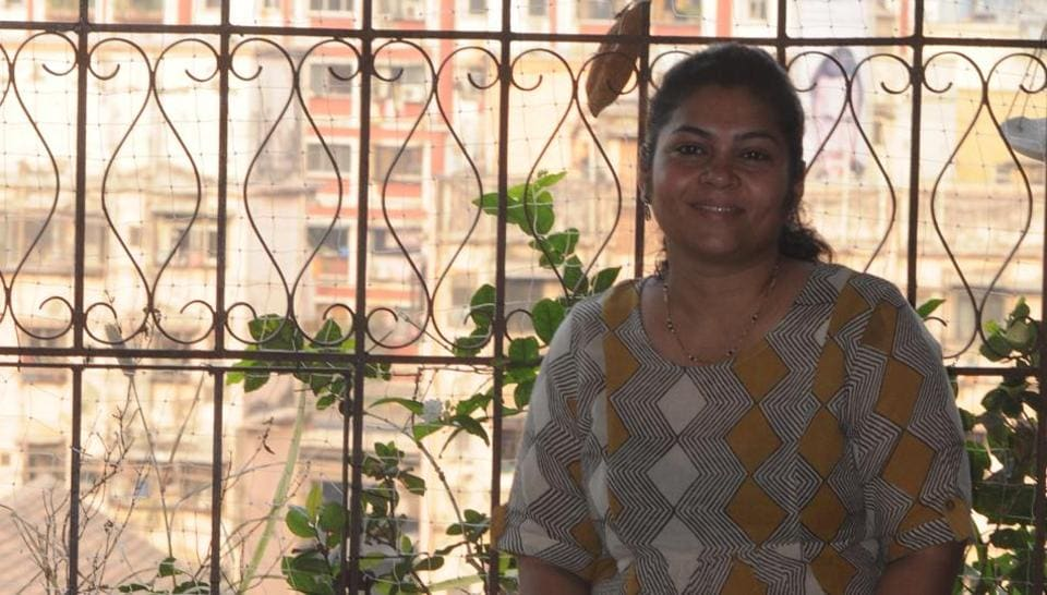 Arundhati Mhatre sits on her balcony among the plants and feeders
