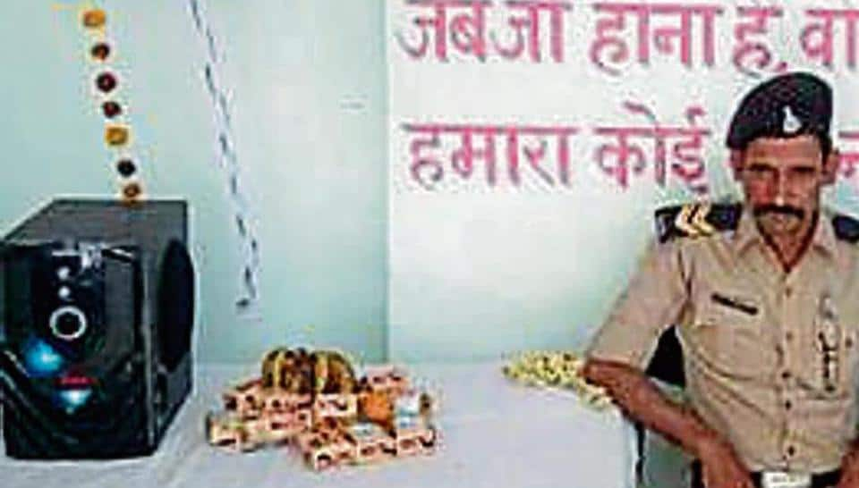 A constable enjoys some tunes in the music chamber in Jabalpur.