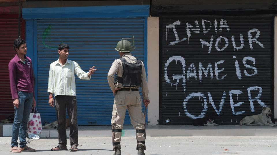A paramilitary soldier stops passersby in downtown Srinagar.