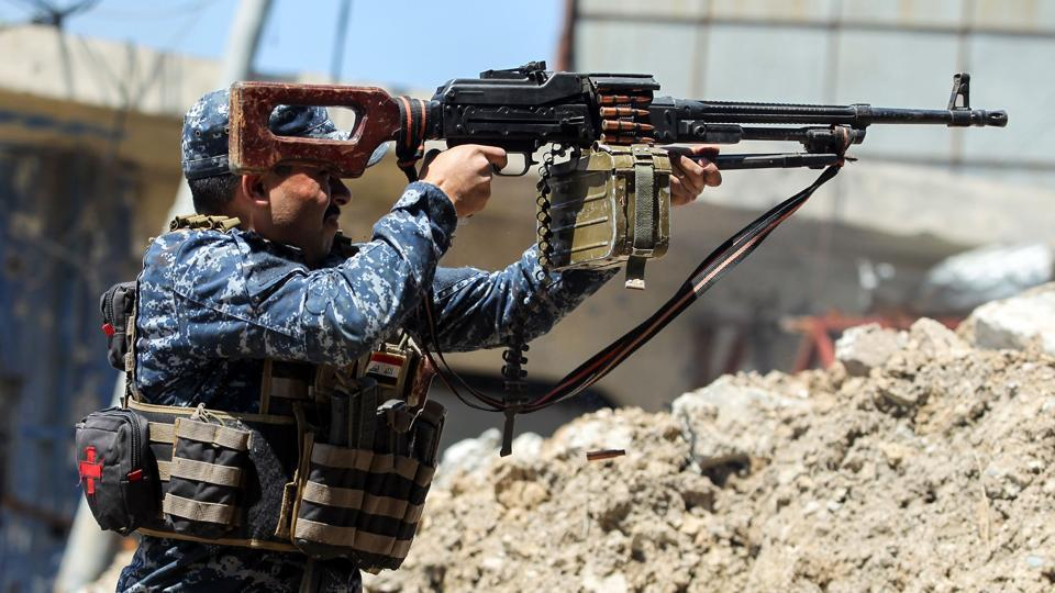 A member of the Iraqi forces shoots suppressive fire while taking cover behind a barrier made of debris in the old city of Mosul during the offensive to recapture the city from Islamic State (IS) group fighters, on April 16, 2017.