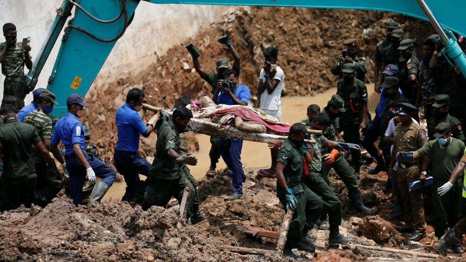 Members of the military carry a dead victim during a rescue mission after a garbage dump collapsed and buried dozens of houses in Colombo. (Dinuka Liyanawatte  / REUTERS)