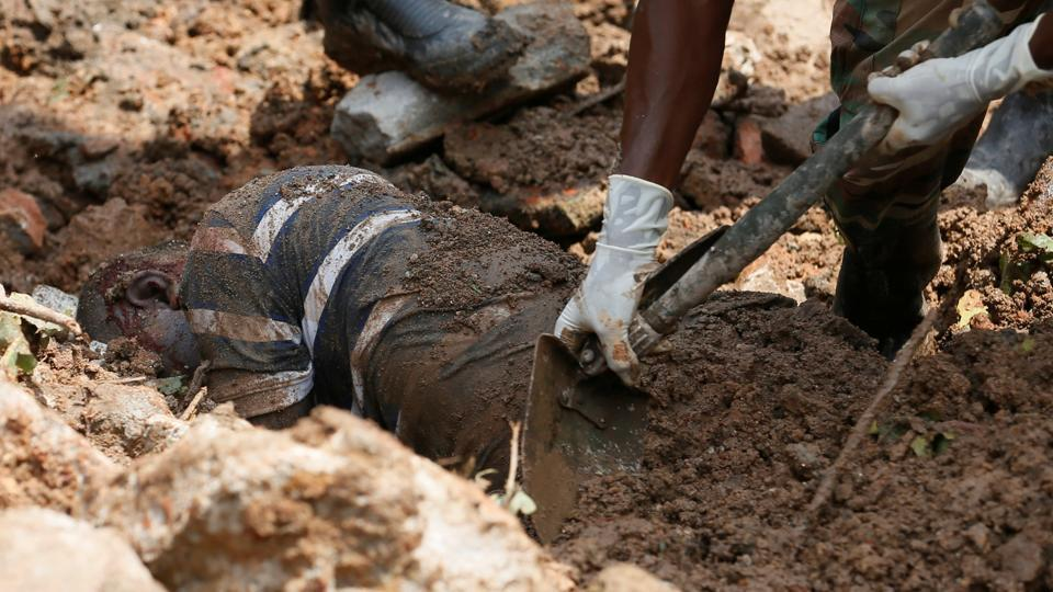 Members of the military dig out the body of a dead victim during a rescue mission after a garbage dump collapsed and buried dozens of houses in Colombo, Sri Lanka . (Dinuka Liyanawatte / REUTERS)