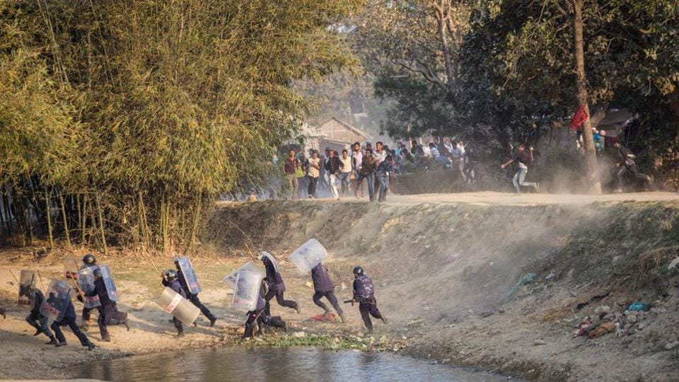Nepalese riot police run for cover as Madhesi activists hurl stones at them in Saptari District, Nepal on March 6.