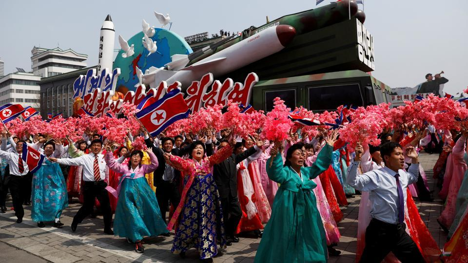 The float in the background is a stylised rocket artillery launcher, adorned with the words 'Pyongjin Line' on its front.  (REUTERS)