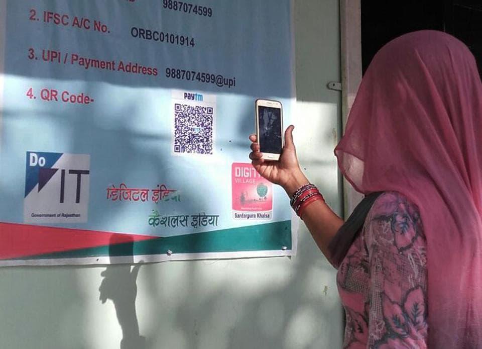 A woman scans bar codes to make payment at a shop at Sardarpura Khalsa, a village in Rajasthan's Hanumangarh district.