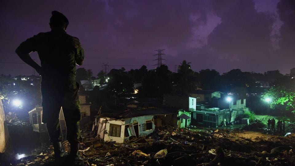 A Sri Lankan military official stands overlooking damaged homes at the site of a collapsed garbage dump in Colombo. (ISHARA S. KODIKARA / AFP)