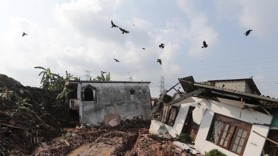Crows fly over a row of houses buried by a collapse of a garbage dump. (Eranga Jayawardena / AP)