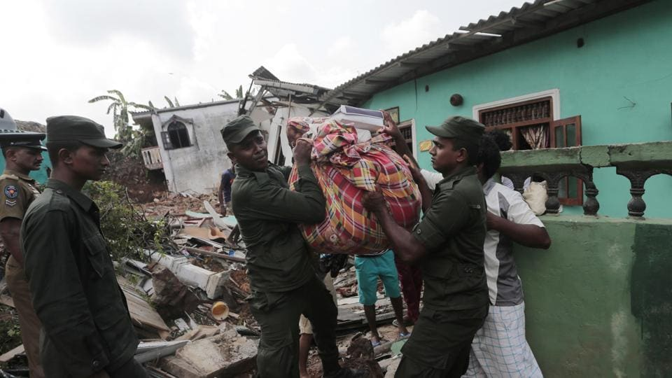 Sri Lankan army soldiers and rescue workers salvage belongings after houses are buried in a collapse of a garbage dump . (Eranga Jayawardena / AP)