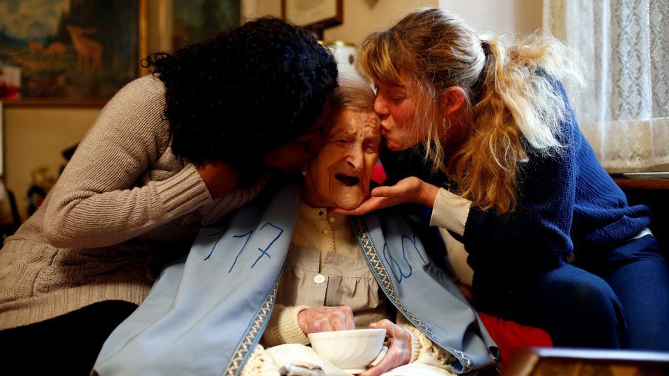 Emma Morano (C) is kissed by her caretakers Malgorzat Ceglinska and Yamilec Vergara during the 117th birthday in her house in Verbania, northern Italy. (Alessandro Garofalo / Reuters File Photo)