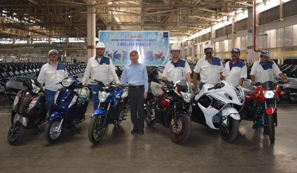 Suzuki Motorcycles management with the company models at the Gurgaon plant.
