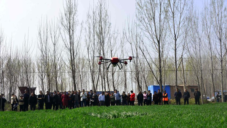 File photo of villagers looking at an agricultural drone being used to spray pesticide on crops in China's Shandong province on April 6, 2017.