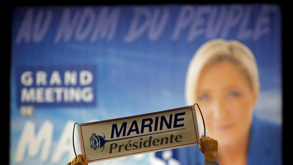 A supporter holds a poster to support Marine Le Pen, French National Front leader and candidate for French presidential election, during a political rally in Perpignan