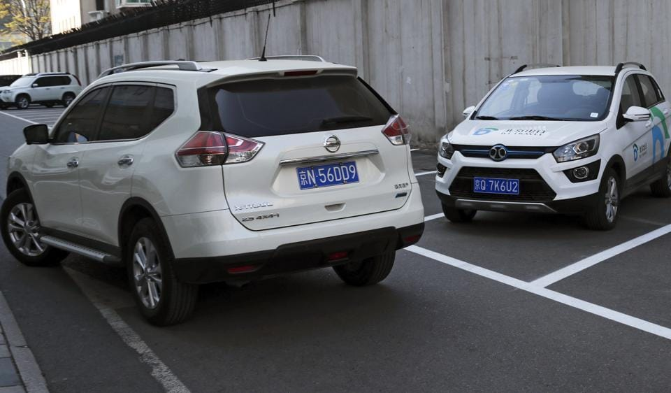 In this April 14, 2017 photo, a SUV vehicle, left, drives past an electric-powered SUV parked outside a shopping mall in Beijing. Automakers face a dilemma in China's huge but crowded market: Regulators are pushing them to sell electric cars, but buyers want gas-guzzling SUVs. This month's Shanghai auto show, the industry's biggest marketing event of the year, will showcase efforts to create electric models Chinese drivers want to buy.