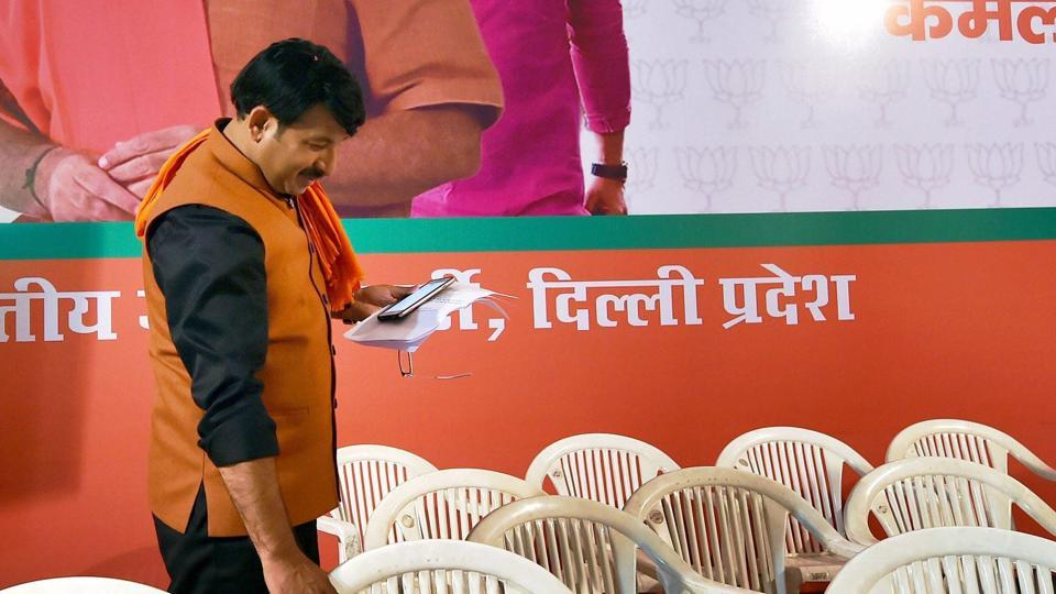 Delhi BJP president Manoj Tiwari adjusts chairs before a press conference during which seven Congress leaders switched to BJP, in New Delhi on Saturday.
