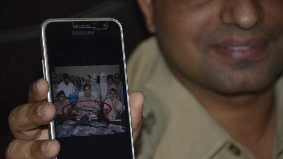 A police official displays a photo found on the smartphone.