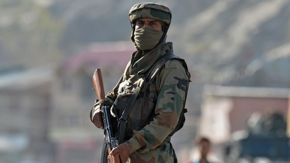 An Indian Army soldier stands guard near the scene of an attack on a Central Reserve Police Force (CRPF) convoy at Panthachowk on the outskirts of Srinagar on April 3.