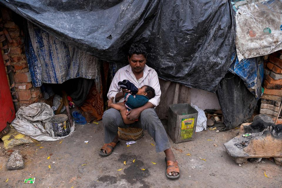 An Indian man feeds bottled milk to his daughter outside his makeshift home in the slums of New Delhi.