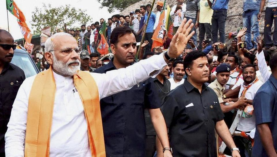 Prime Minister Narendra Modi waves at people during his visit to Lord Lingaraj temple in Bhubaneswar on Sunday.