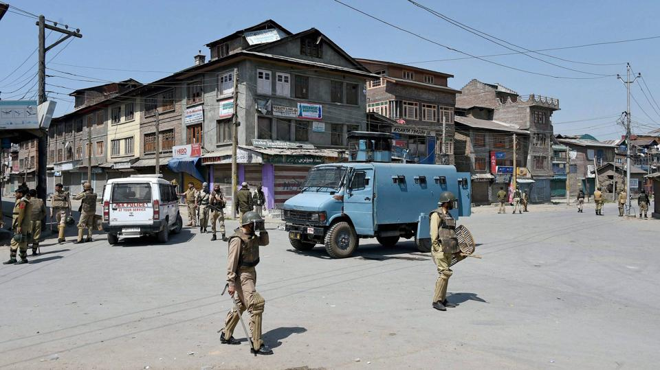 Police and CRPF personnel stand guard during restrictions imposed by the government authorities and strike call given by Hurriyat Conference following the killing of a youth, in Batamaloo. (S Irfan / PTI)