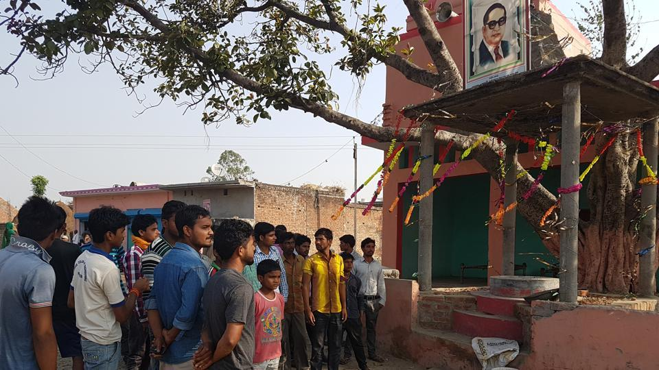 Villagers look on as the administration officials remove the disfigured statue of Ambedkar at Mirzapur Sadat village in Haridwar .