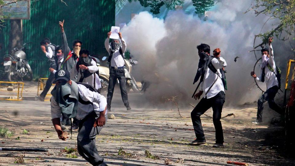 Student throwing stones on police amid heavy tear smoke during a clash with police outside SP college in the vicinity of Lal Chowk in Srinagar on Monday.