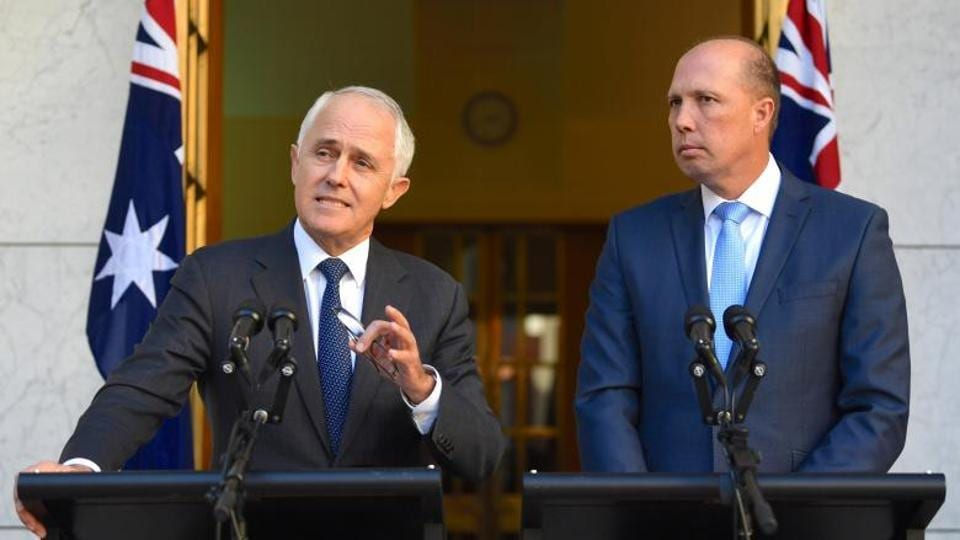 Australia's Prime Minister Malcolm Turnbull speaks as Immigration Minister Peter Dutton listens on during a media.