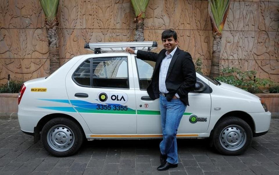 Bhavish Aggarwal, CEO and co-founder of Ola, an app-based cab service provider, poses in front of an Ola cab in Mumbai.