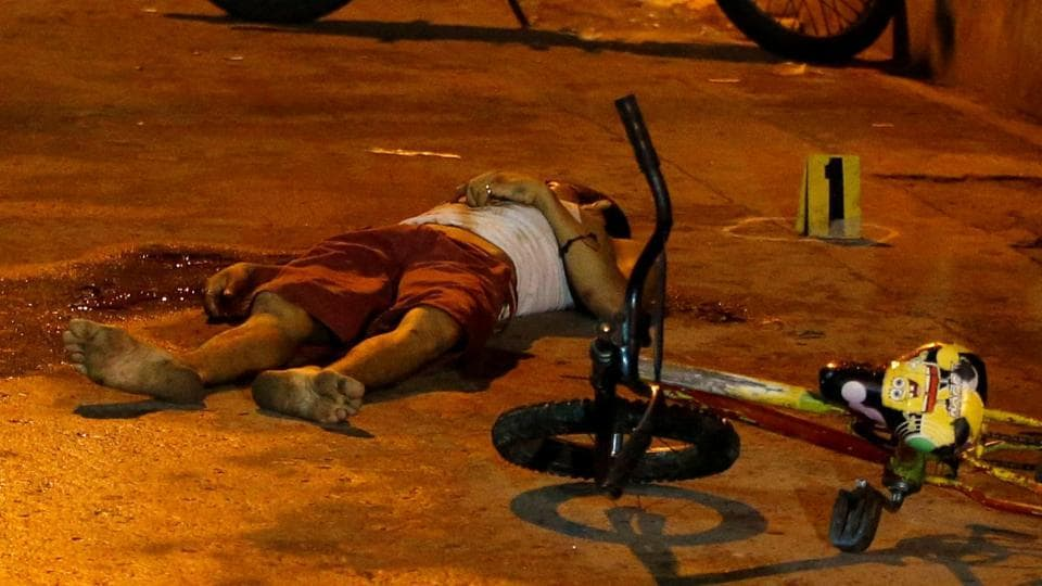 The body of a man whom police said killed during a drug related vigilante killing, lies next to his bicycle in Pasig, Metro Manila, Philippines on February 1.