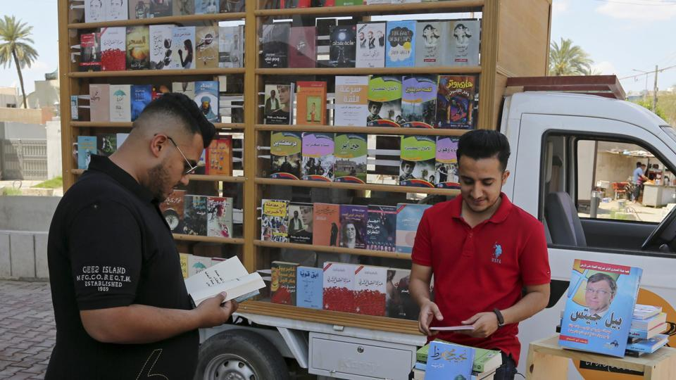 Ali al-Moussawi (R), the owner of a mobile book truck, arranges his books on a street in Baghdad, Iraq.
