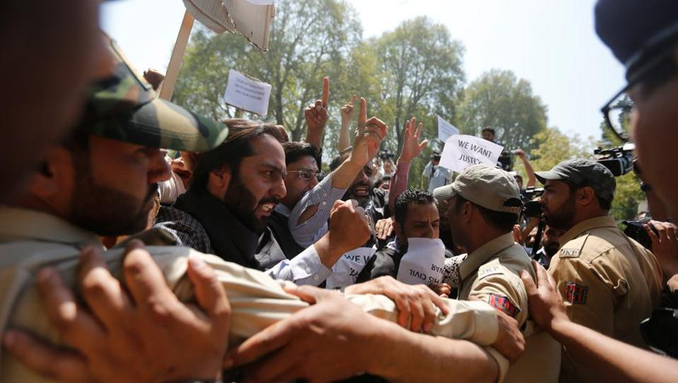 Police try to stop supporters of National Conference (NC) party during a protest against what the supporters say was the use of force on  students, in Srinagar.
