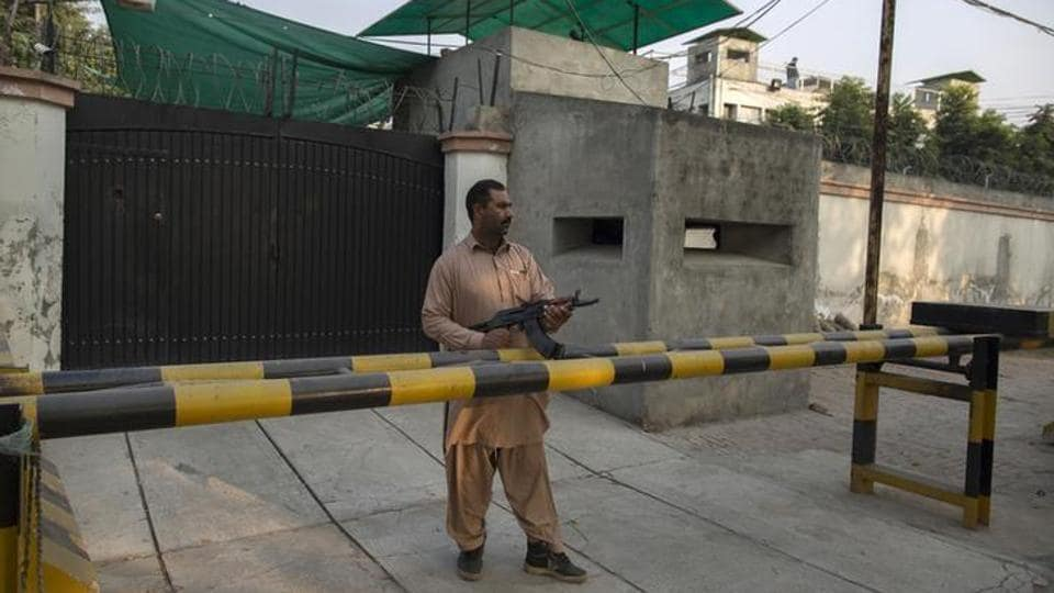 File photo of a security guard from the Ahmadi community standing outside the Batul Noor mosque in Lahore in December 2013.