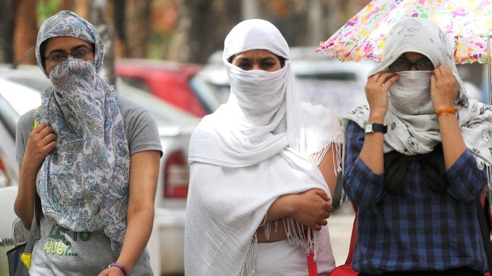 Girls cover their faces as Chandigarh reels under extreme weather conditions on Wednesday.